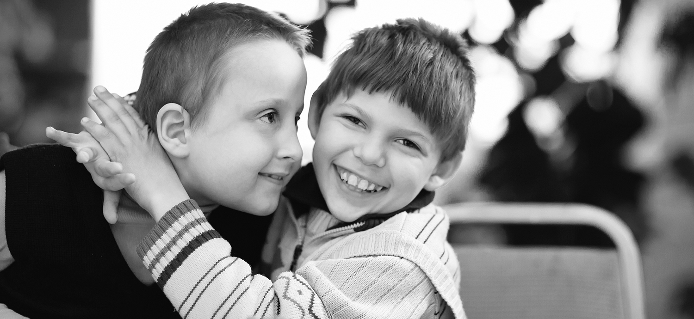 two children smile and hug